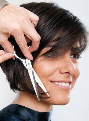 Парикмахер выполняет градуирование кончиков волос