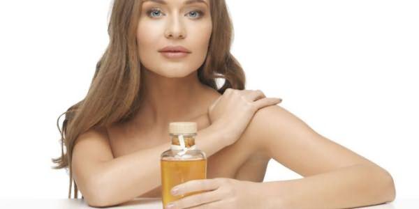 Девушка держит в руке бутылку масла
