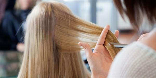 Стилист стрижет волосы девушки