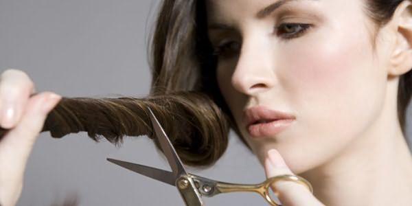 Девушка обрезает секущиеся кончики