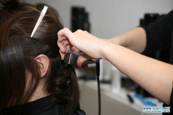 Мастер выпрямляет волосы клиентки