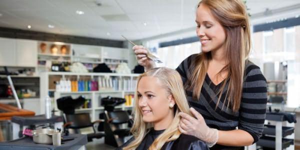 Парикмахер окрашивает волосы клиентки