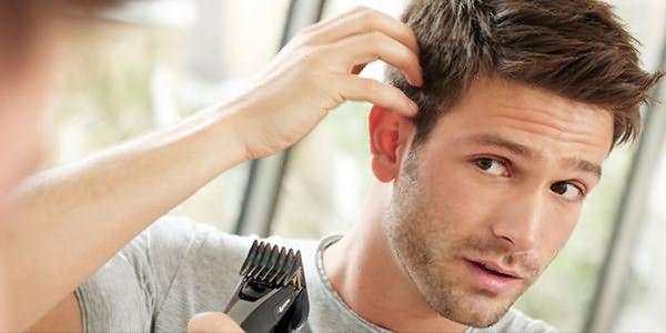 Мужчина подстригает волосы машинкой самостоятельно