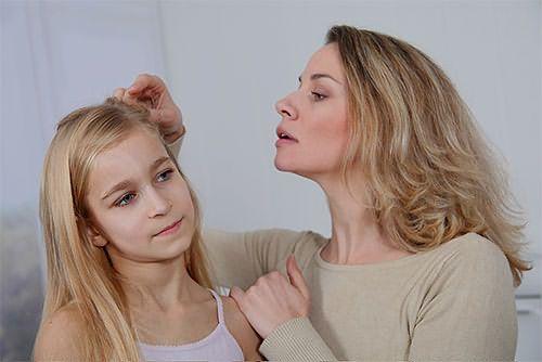 Женщина осматривает голову девочки