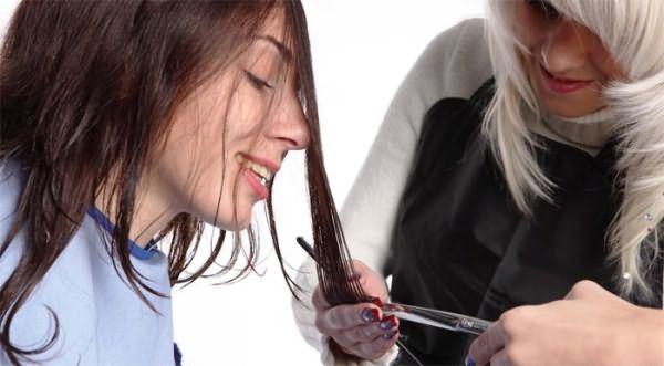 Парикмахер подстригает волосы