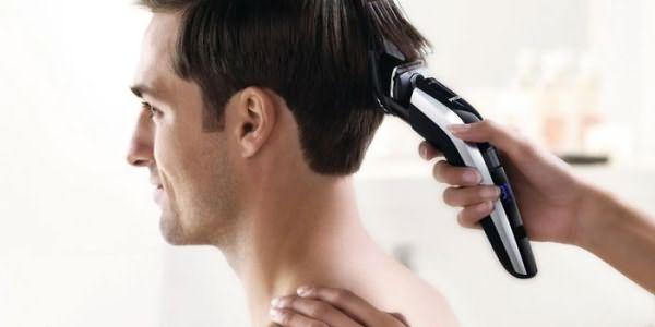 Мужчине стригут волосы машинкой