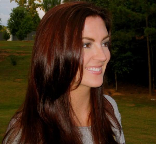 Девушка на фоне природы с каштановыми волосами улыбается и смотрит в сторону