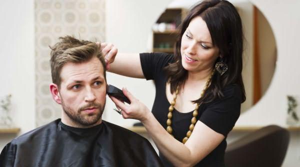Девушка подстригает мужчину машинкой