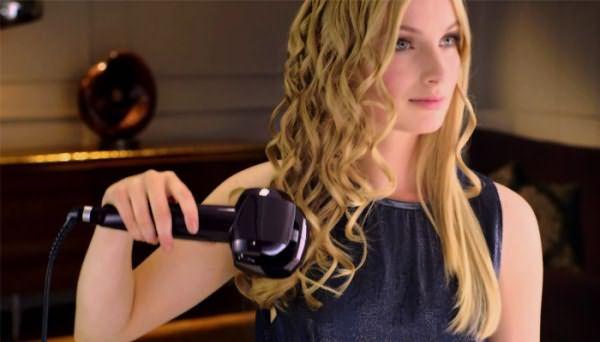Девушка выпрямляет волосы стайлером
