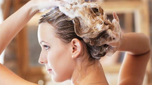 Женщина использует шампунь от перхоти